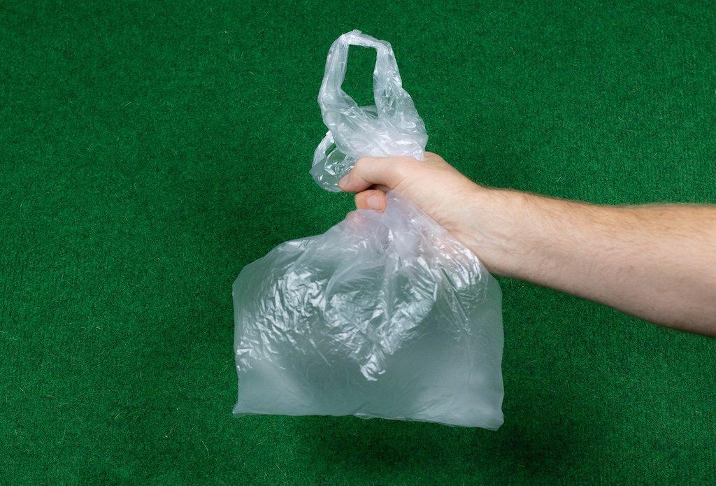 Ein Mann hält eine Plastiktüte vor grünem Hintergrund