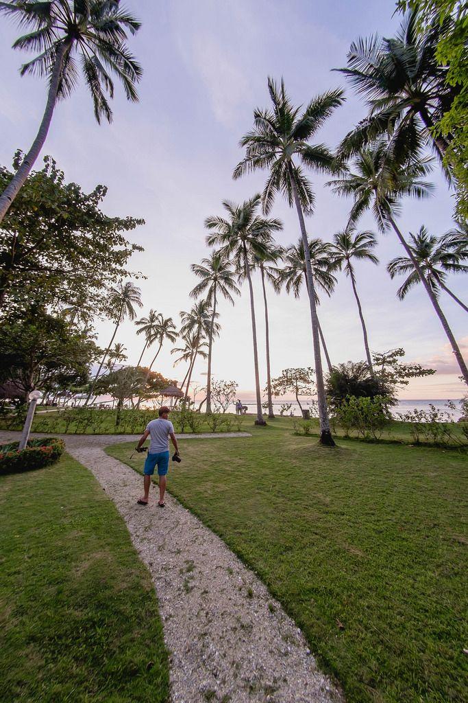 Ein Mann im Sonnenuntergang auf einer tropischen mit Palmen bewachsener Insel Punta Bulata
