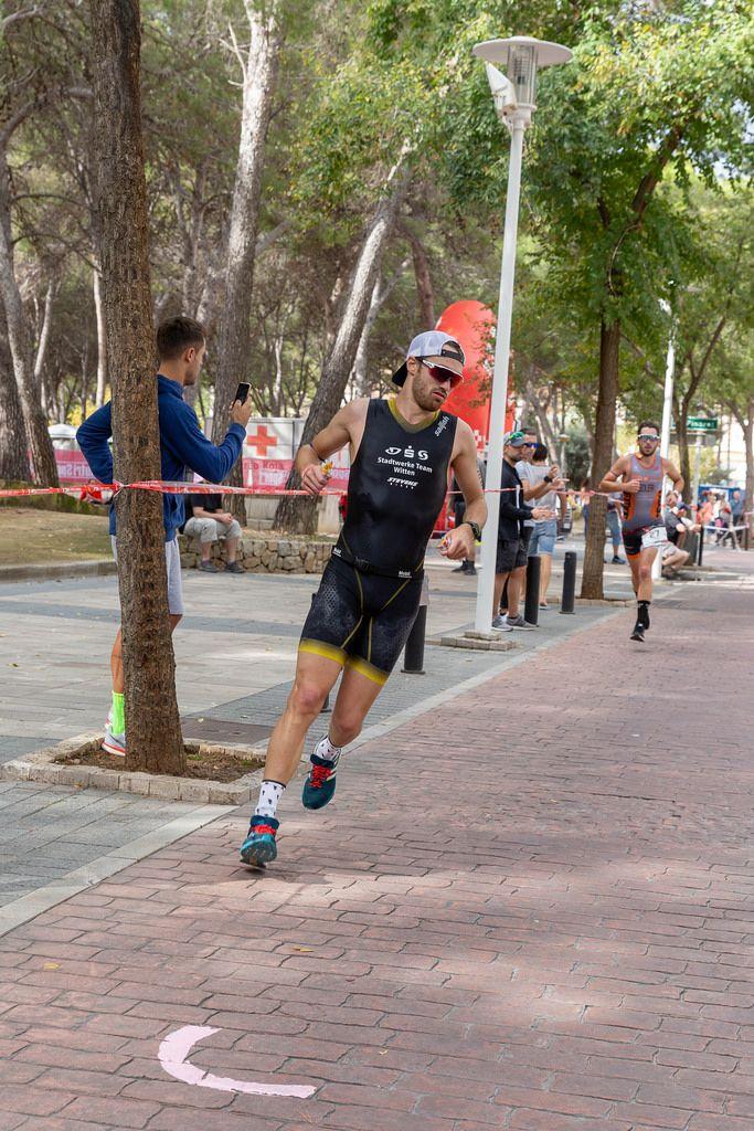 Ein Mann in schwarzem Equipment, Sonnenbrille und Schirmmütze läuft bei einem Triathlon in Paguera