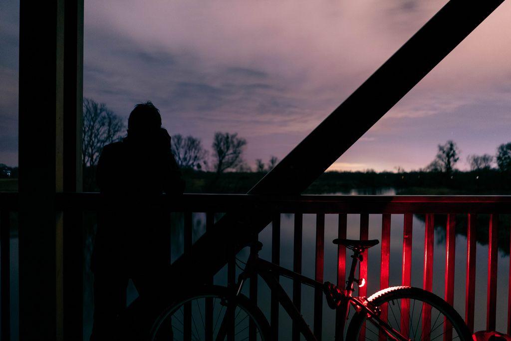Ein Mann schießt ein Foto von einer Holzbrücke aus, neben einem Fahrrad mit rotem Licht