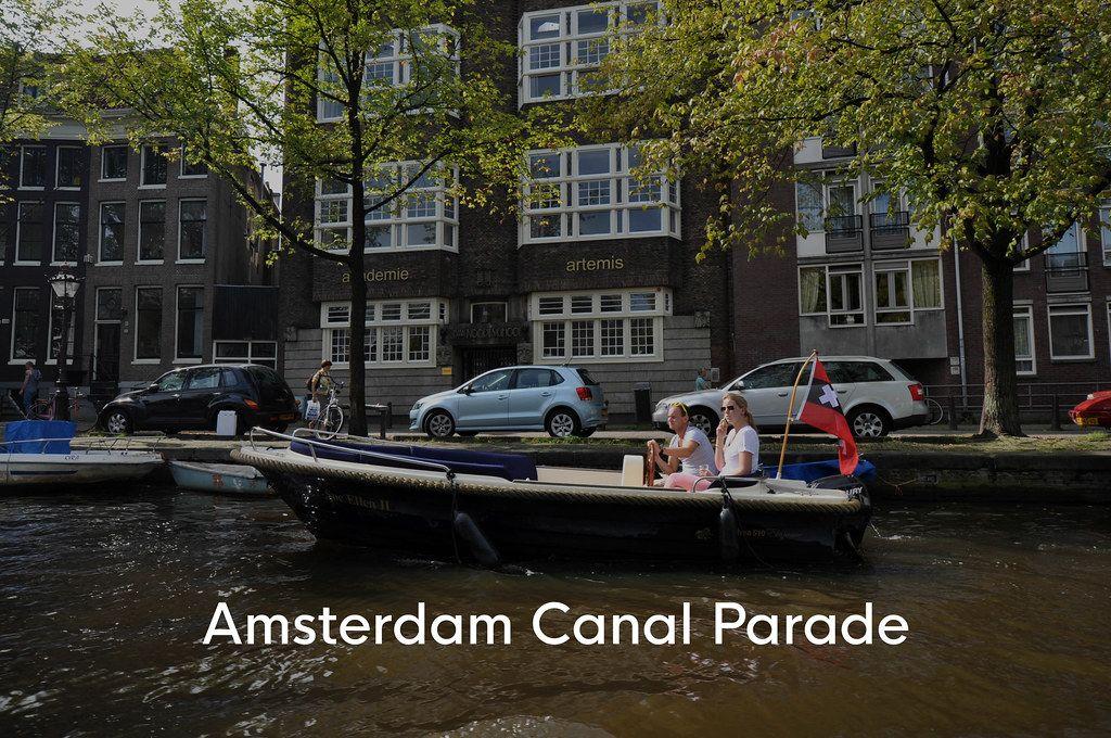 Ein Paar im Motorboot auf den Amsterdamer Grachten, neben dem Bildtitel Amsterdam Canal Parade, die Teil des Gay Pride - LGBT - Festivals ist