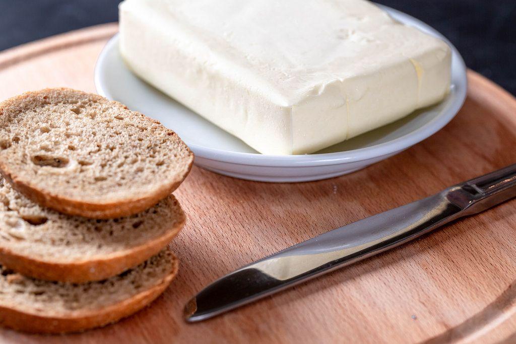 Ein Paket Butter mit ein Paar Scheiben Brot und einem messer auf einem Brettchen