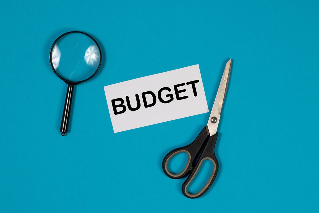 Ein Papier mit der Aufschrift Budget, einer Schere und einer Lupe auf blauem Hintergrund