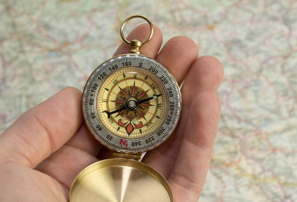 Ein Reisender hält einen Kompass in der Hand