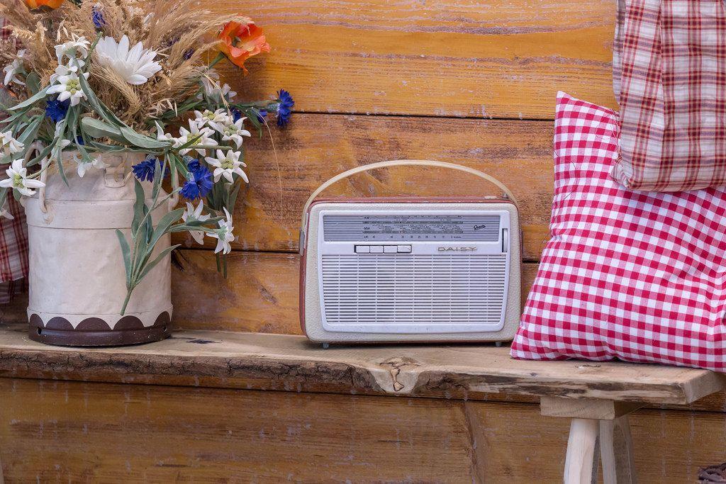 Ein Retro-Radio vor Holzwand mit Feldblumen und rot weiß kariertem Kissen