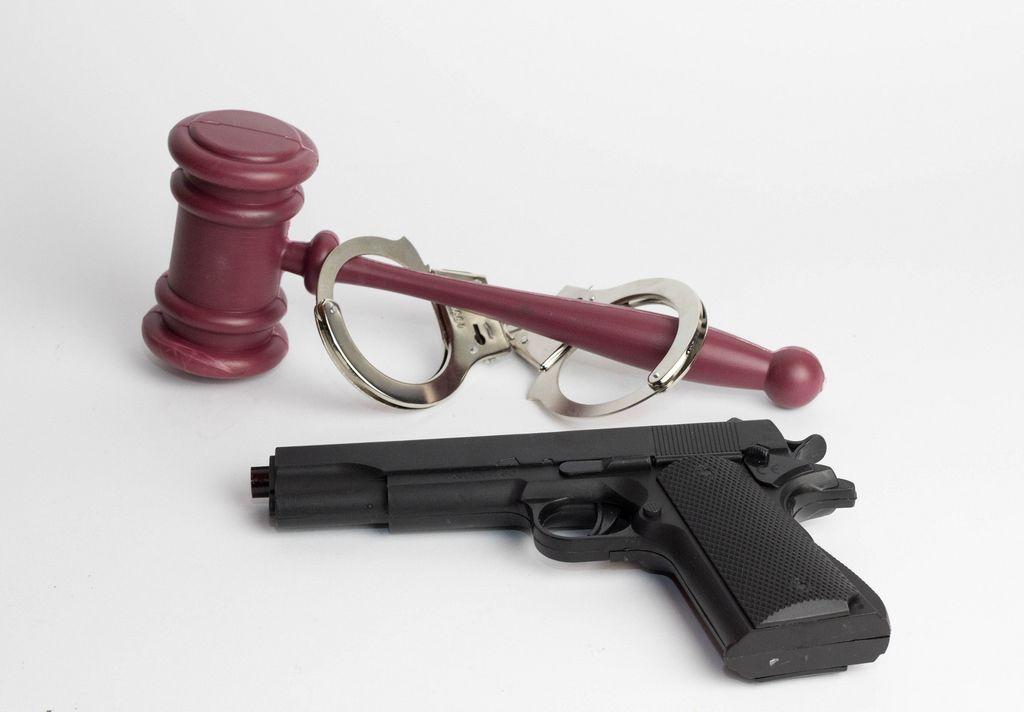 Ein Richterhammer mit Handeschellen und einer Pistole