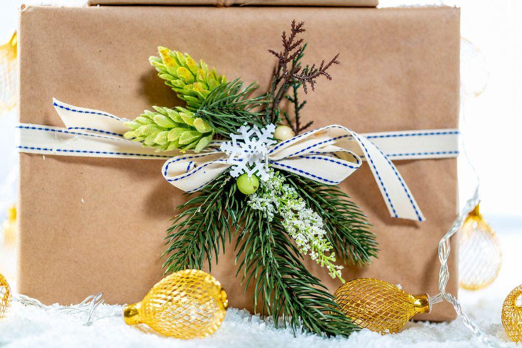 Ein schön verpacktes Weihnachtsgeschenk mit Kranz geschmückt