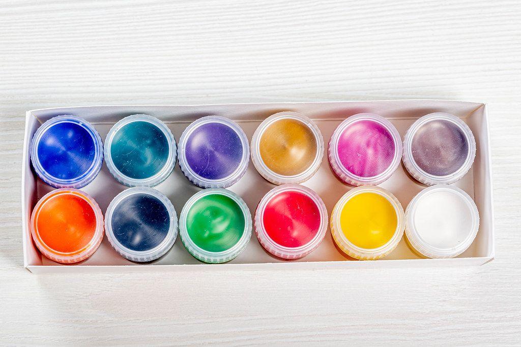 Ein Set von bunten Farben für Malen auf braunem Holztisch