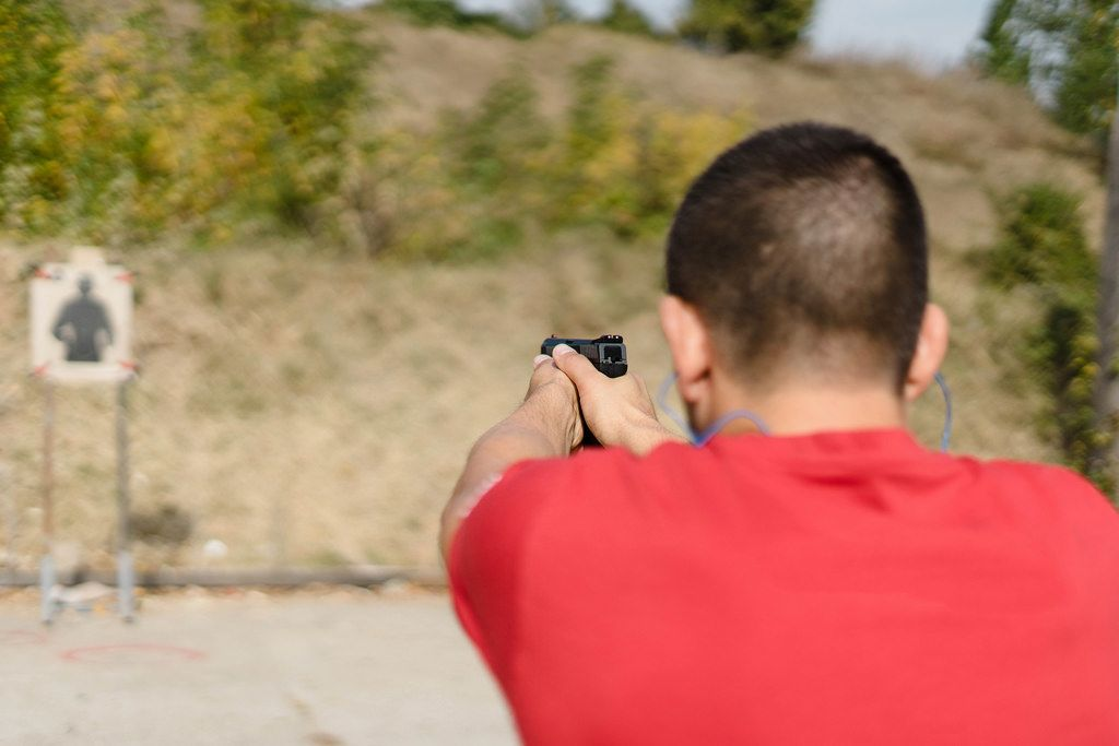 Ein Sportschütze schießt mit einer Pistole auf eine Zielscheibe