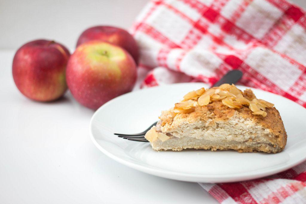 Ein Stück Apfelkuchen mit Mandeln auf einem weißen Teller mit Äpfeln und einem Tuch im Hintergrund
