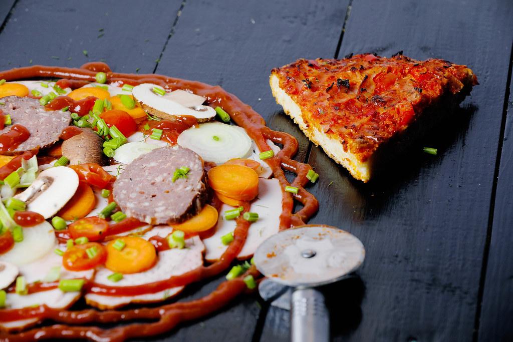 Ein Stück gebackene Fertigpizza neben rohen Zutaten für eine selbstgemachte Pizza