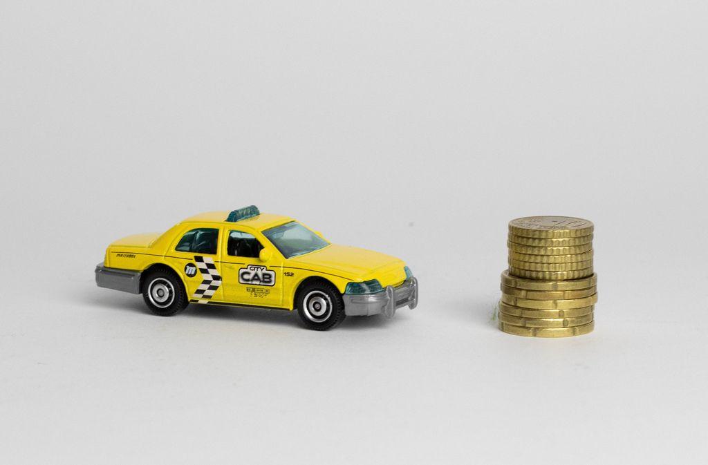 Ein Taxi mit einem Stapel Münzen auf weißem Hintergrund