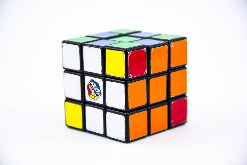 Ein ungelöster Rubiks Cube Rätselwürfel auf weißem Hintergrund