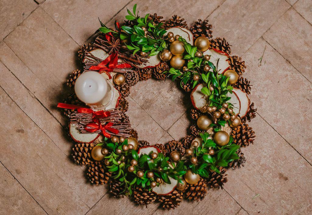 Ein Weihnachtskranz mit Mistelzweigen, goldenen Kugeln, Tannenzapfen und einer Kerze