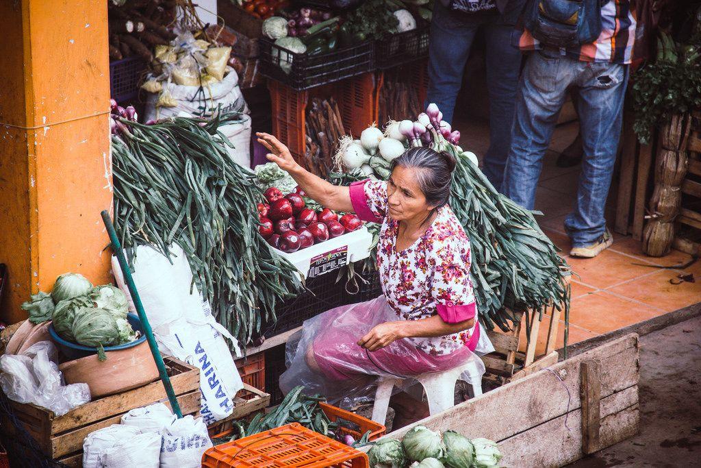 Eine Alte Dame verkauft Gemüse und Obst auf dem Markt