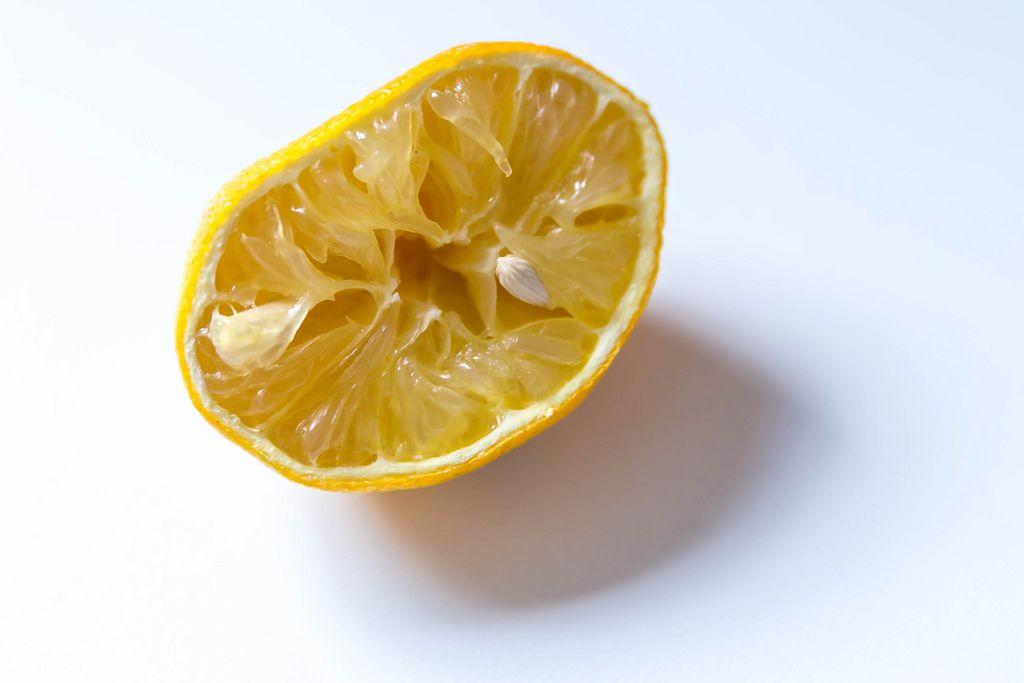 Eine ausgepresste Zitrone vor weißem Hintergrund