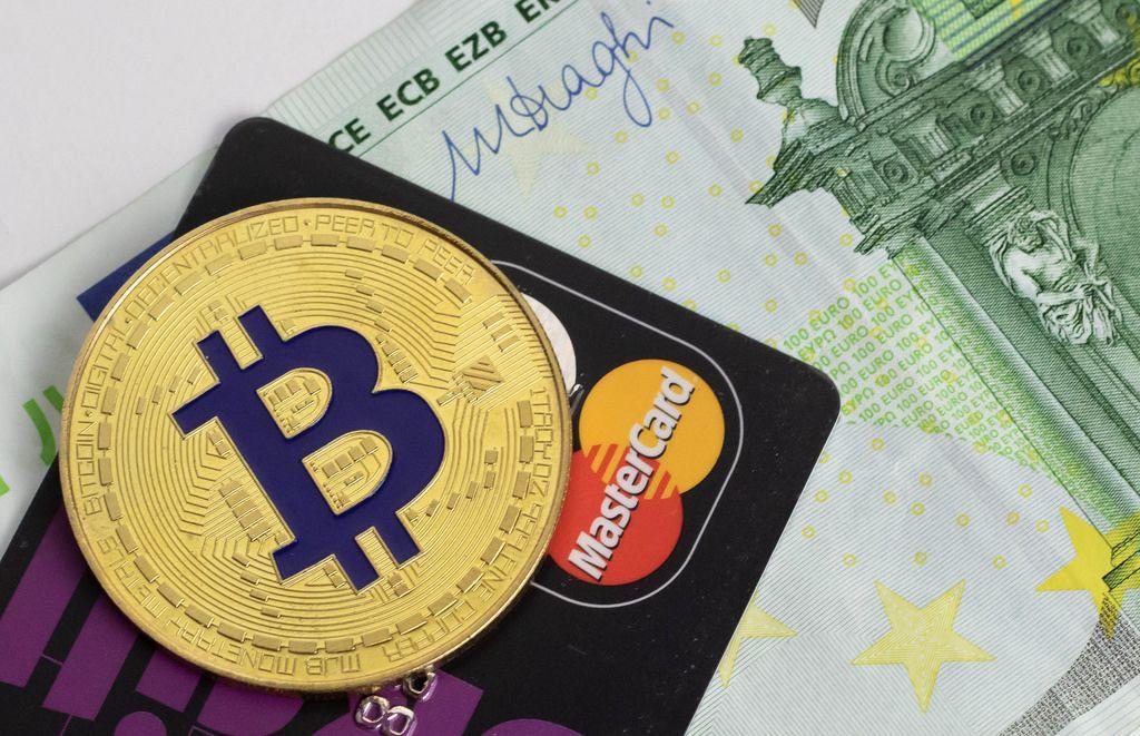Eine Bitcoin-Münze auf einer schwarzen Kreditkarte und einem Geldschein