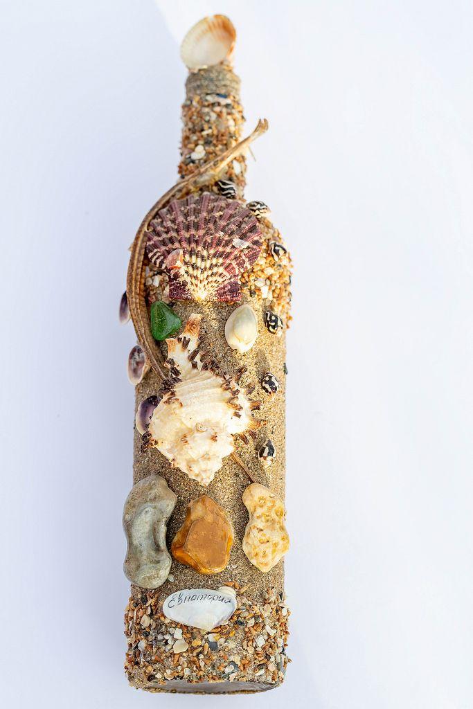Eine Flasche mit Ozeanschmuck  - Muscheln, Sand und eine Seenadel auf weißem Hintergrund
