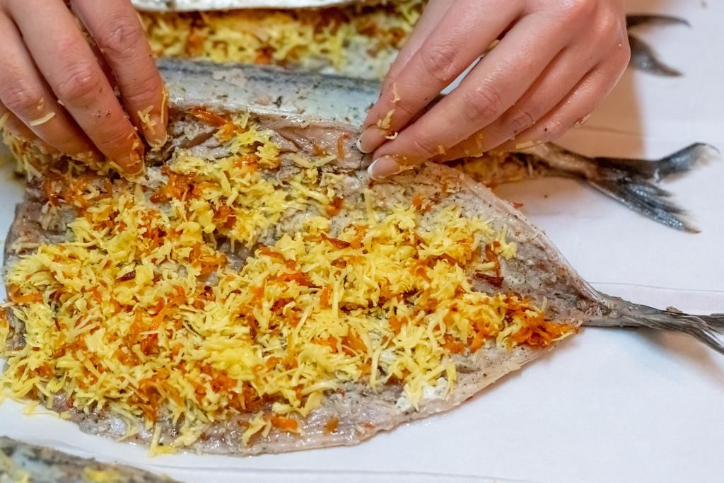 Eine Frau füllt eine Makrele mit Käse