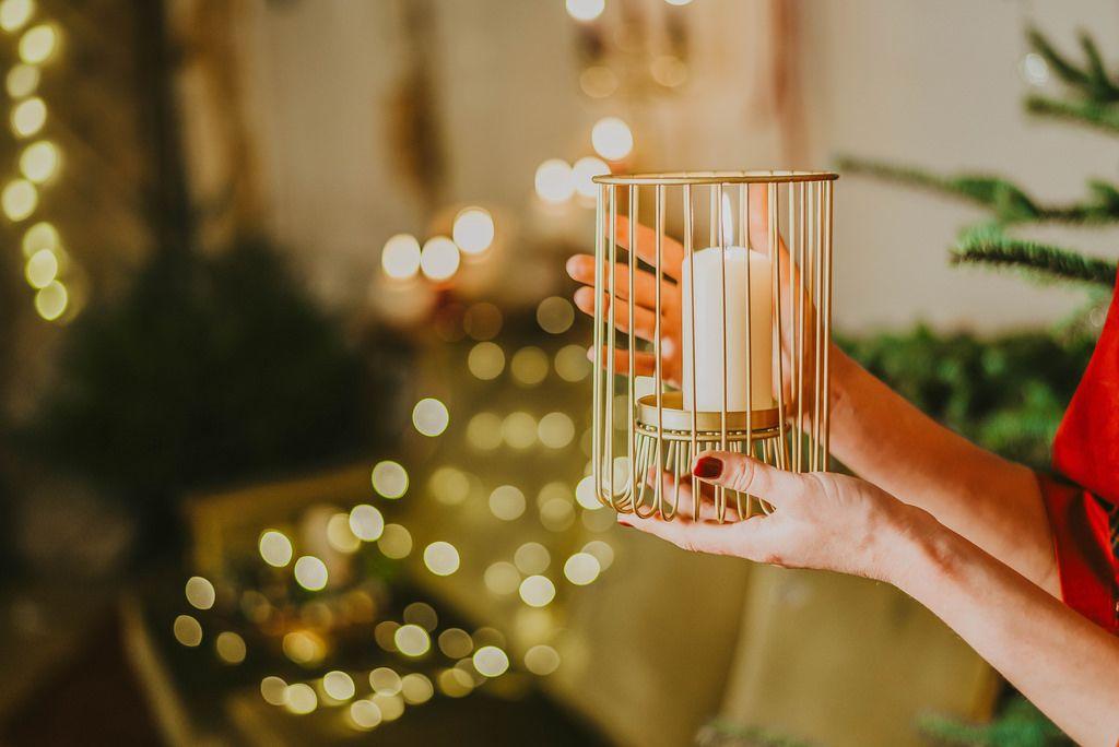 Eine Frau hält eine Adventskerze mit Lichtern im Hintergrund