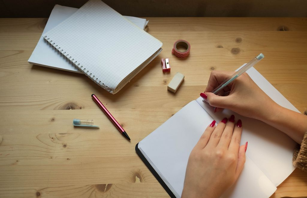 Eine Frau schreibt in einem Notizheft mit Bleistift, Radierer und Anspitzer auf einem Holztisch