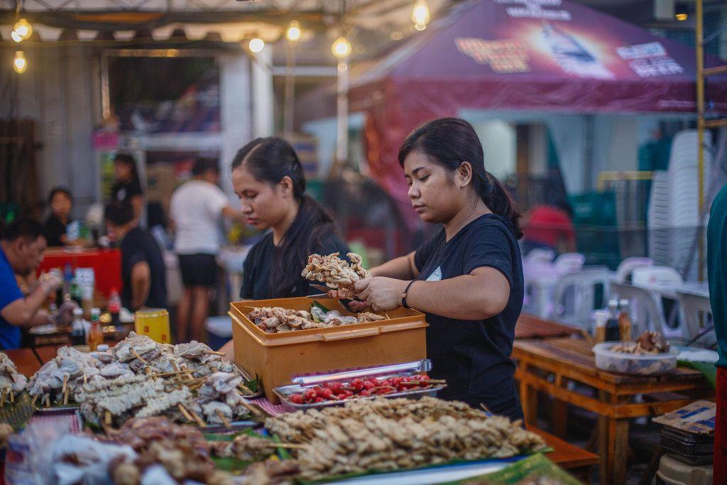 Eine Frau verkauft gegrilltes Fleisch am Spieß