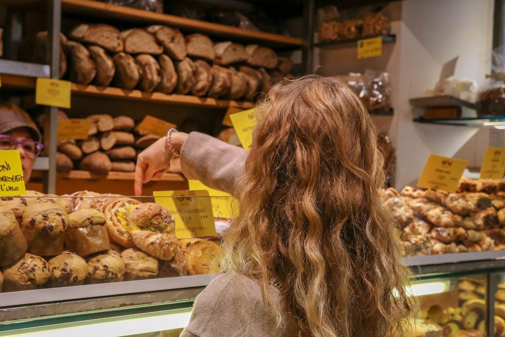 Eine Frau wählt ein Brot bei einem Bäcker auf dem Markt in Rom