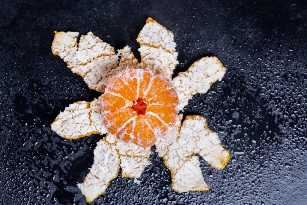 Eine frische saftige Mandarine auf schwarzem Hintergrund
