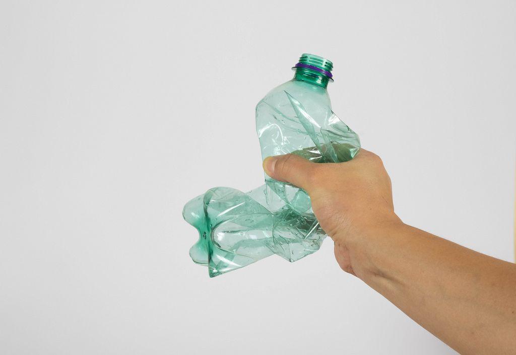 Eine Hand die eine Plastikflasche zerquetscht auf weißem Hintergrund