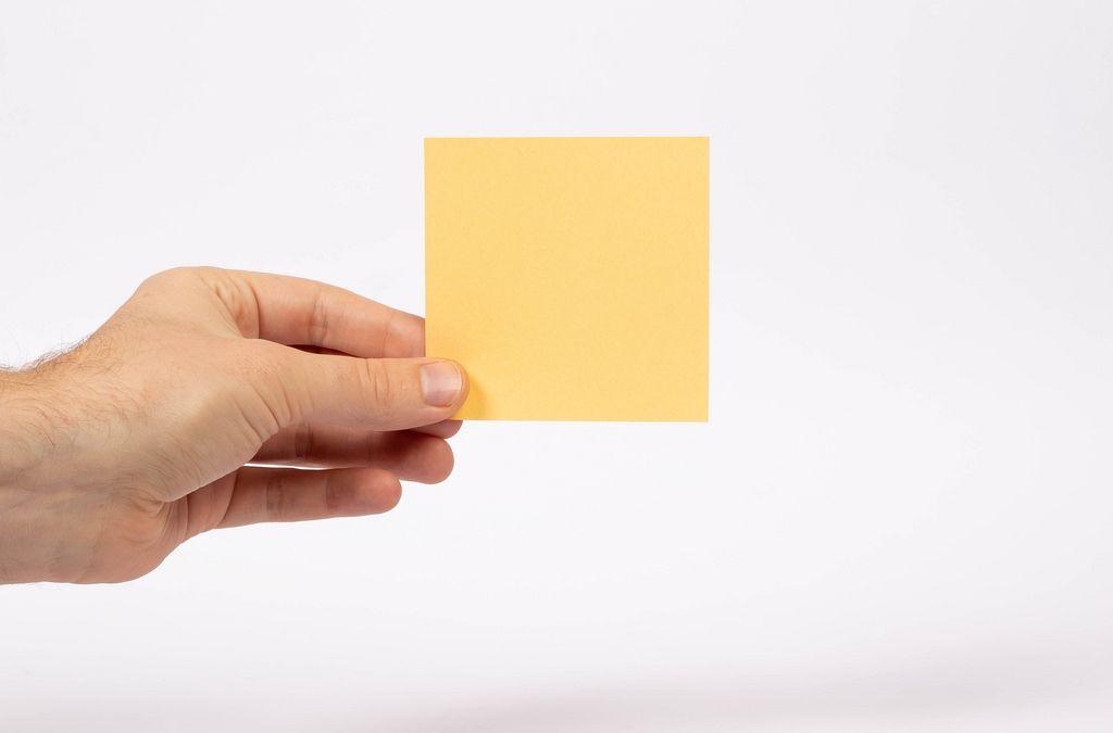 Eine Hand hält ein Notizblatt