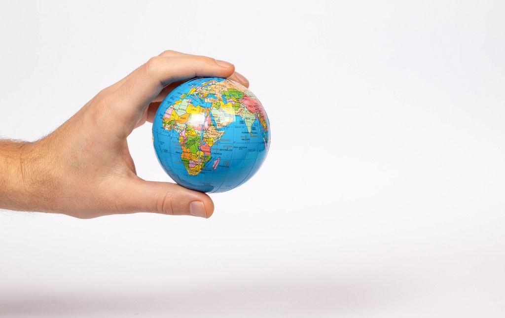 Eine hand hält einen Globus auf weißem Hintergrund