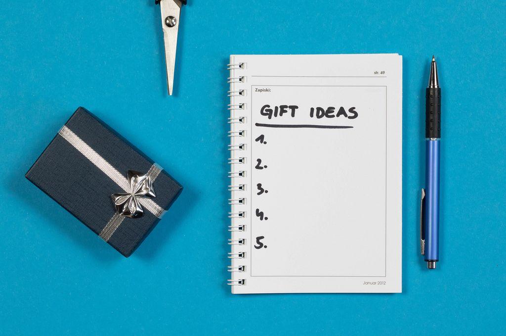 Eine Liste mit Geschenkideen auf einem Notizheft mit einer Schere, Stift und Geschenk auf blauem Hintergrund