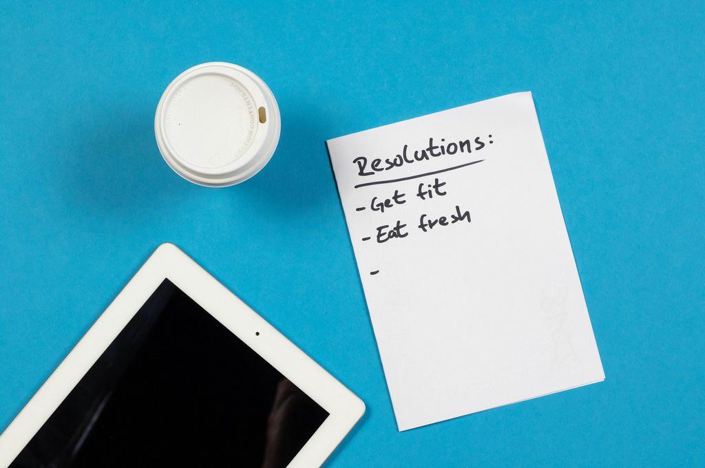 Eine Liste mit Neujahrsvorsetzen, einem Becher Kaffee und iPad auf blauem Hintergrund