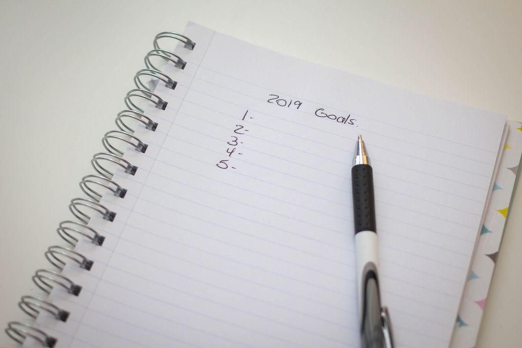 Eine Liste mit Zielen für das neue Jahr 2019 auf einem Notizbuch mit Kugelschreiber