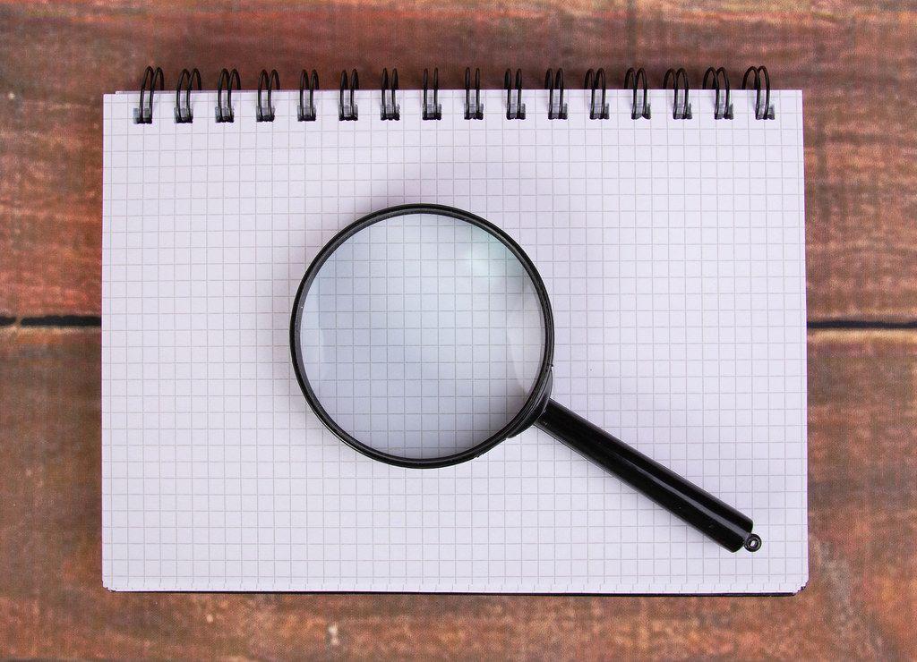 Eine Lupe liegt auf einem leeren Schreibblock mit Karokästchen