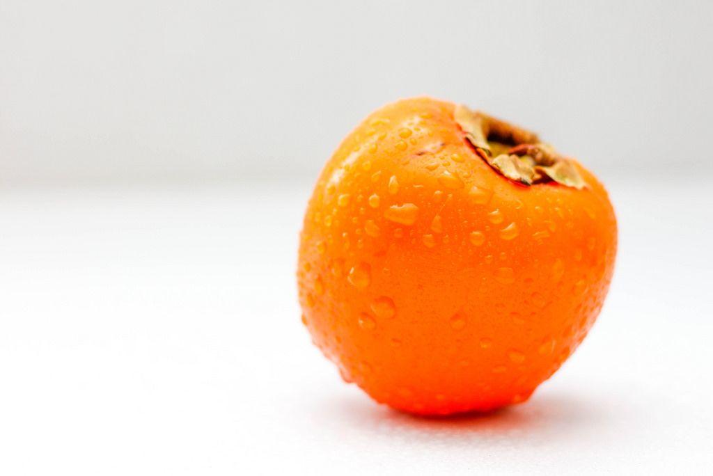 Eine nasse Kaki-Frucht vor weißem Hintergrund