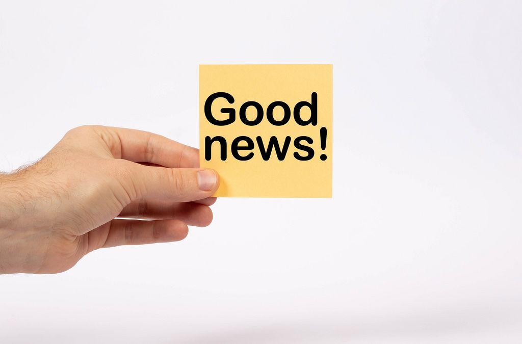 Eine Notiz mit der Aufschrift Good News in der Hand gehalten auf weißem Hintergrund