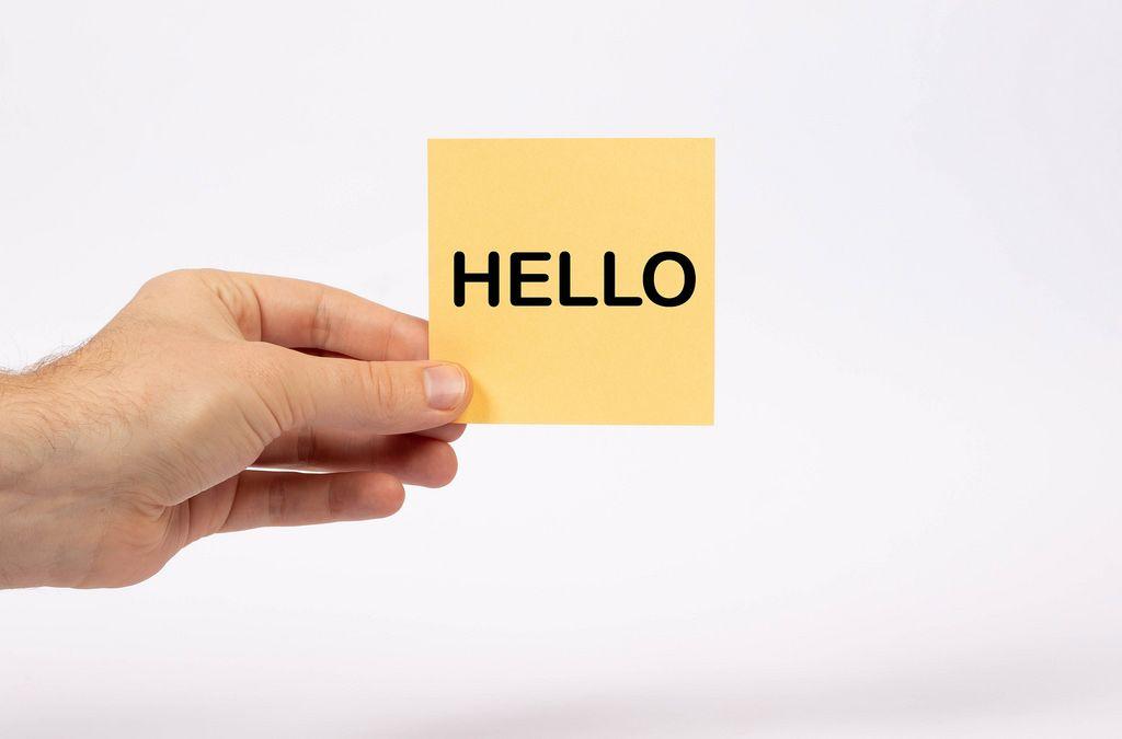Eine Notiz mit der Aufschrift Hello  in der Hand gehalten auf weißem Hintergrund