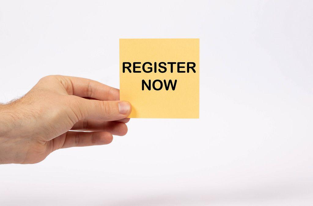Eine Notiz mit der Aufschrift Register Now in der Hand gehalten auf weißem Hintergrund