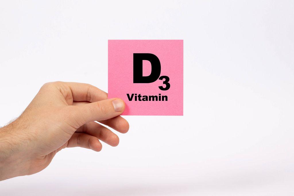 Eine Notiz mit der Aufschrift Vitamin D3 in der Hand gehalten auf weißem Hintergrund