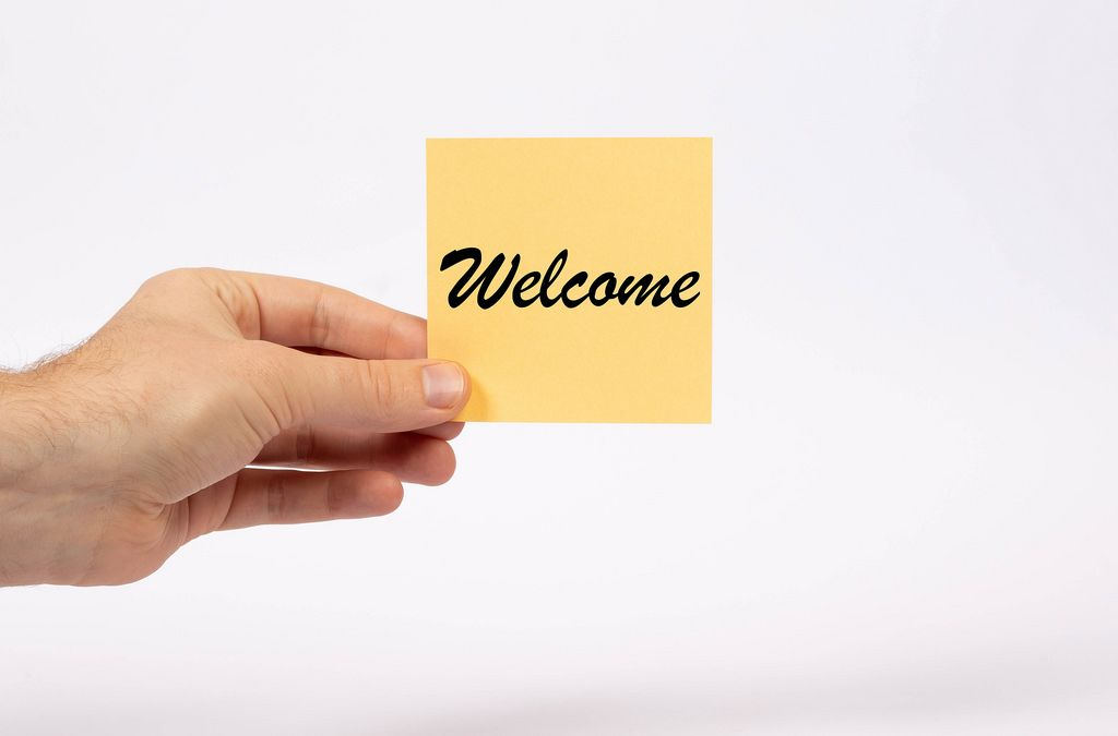 Eine Notiz mit der Aufschrift Welcome in der Hand gehalten auf weißem Hintergrund