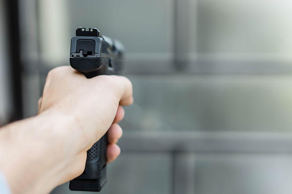 Eine Pistole in der Hand aus der Sicht des Schützen