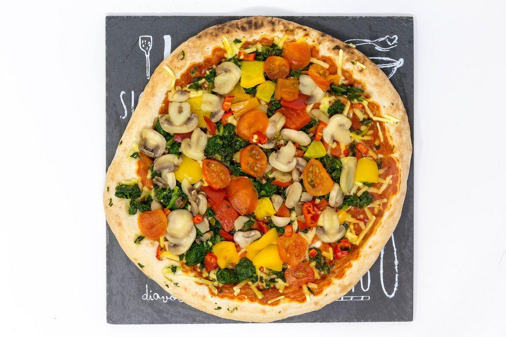Eine Pizza mit frischem Gemüse - Pilze, Kirschtomaten, Spinat und Parpika - Nahaufnahme