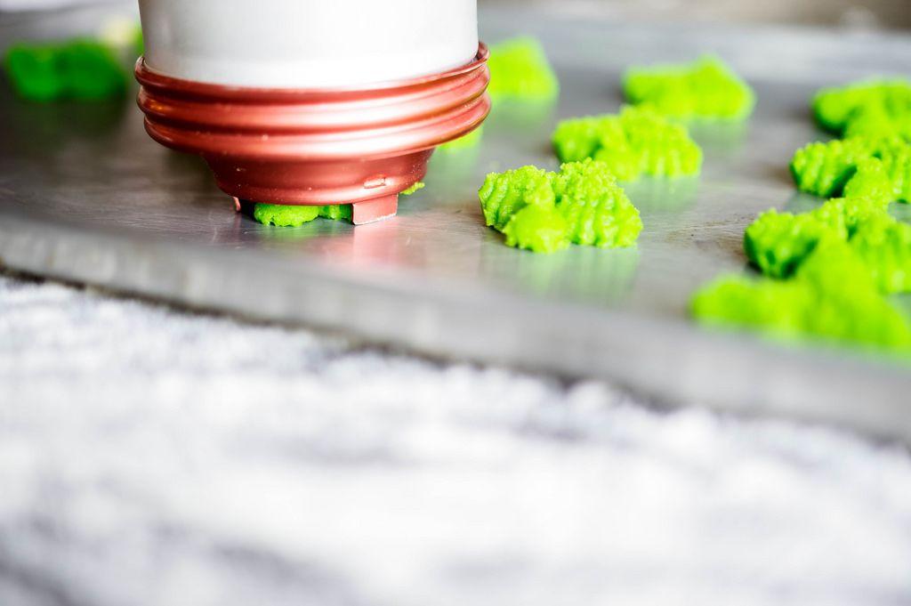 Eine Plätzchen-Spritze spritzt grüne Plätzchen auf ein Backblech