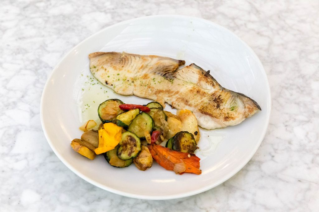 Eine Portion gegrillter Schwertfisch mit blanchiertem Gemüse auf einem weißen Teller