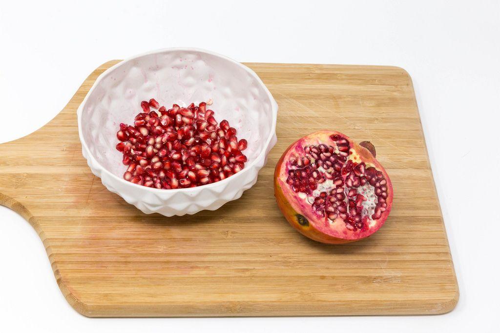 Eine Schale mit Granatapfelkernen und halbiertem Granatapfel auf Holzbrett