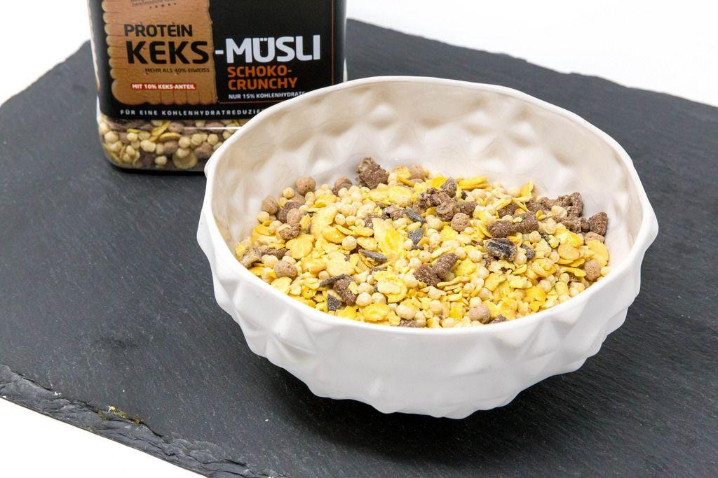 Eine Schale mit Layenberger Low Carb Protein Keks-Müsli in der Variation Schoko Crunchy mit Verpackung
