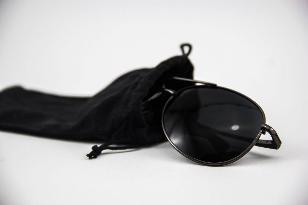 Eine schwarze Piloten-Sonnenbrille in einem Sonnenbrillen-Etui auf weißem Hintergrund