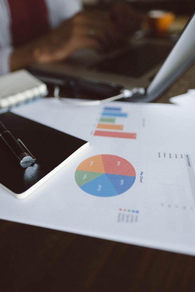 Eine Statistik auf einem Dokument mit einem Mann der an einem Computer arbeitet im Hintergrund
