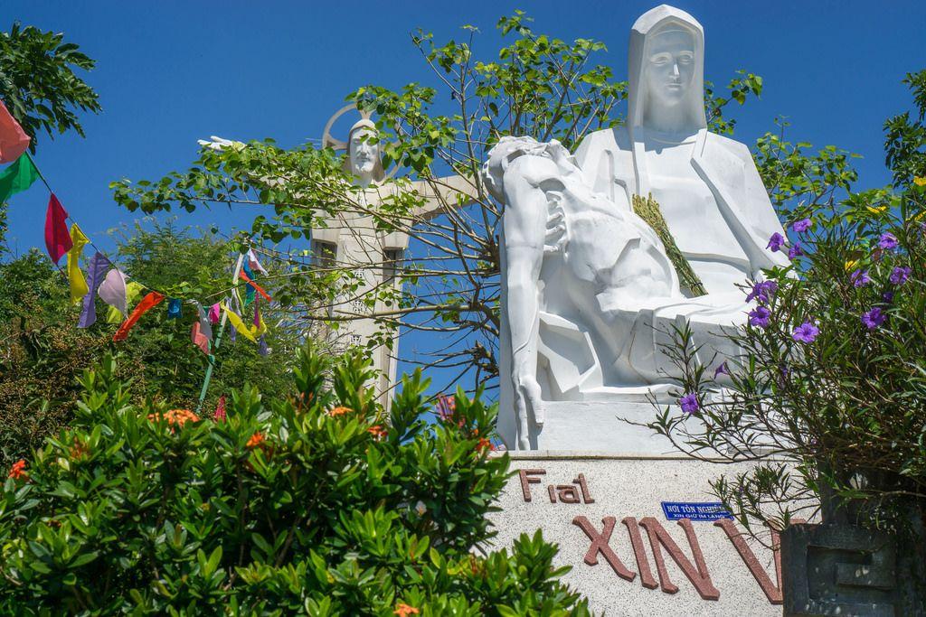 Eine Statue der heiligen Maria mit dem Jesus Christus Monument im Hintergrund in Vung Tau